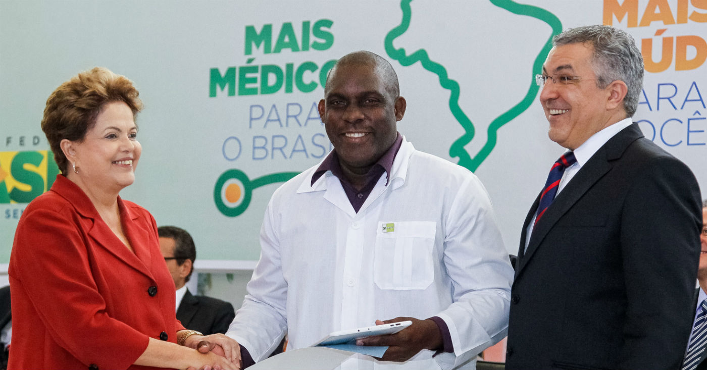 Presidenta Dilma Rousseff, médico cubano, Juan Delgado e o Ministro da Saúde Alexandre Padilha durante sanção da lei que institui o Programa Mais Médicos. Foto: Roberto Stuckert Filho / PR